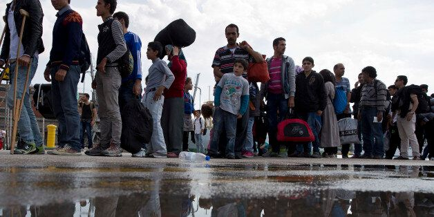 Migrants and refugees wait for a bus after their arrival with a ferry from the Greek island of Lesbos...