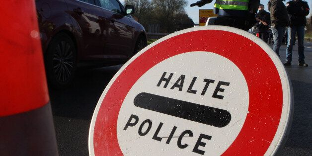 A French police officer monitors slows down the traffic at the border between France and Belgium in Neuville-en-Ferrain,...