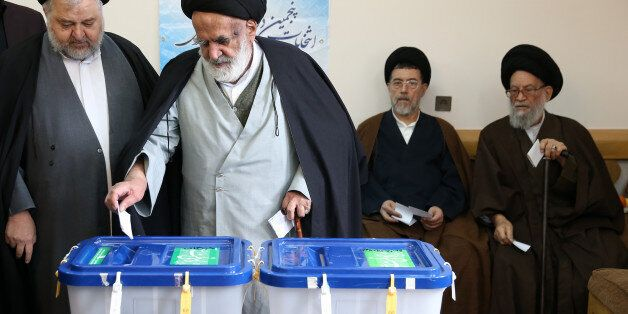 Iranian clergymen vote in the parliamentary and Experts Assembly elections at a polling station in Qom,...