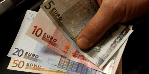 A customer receives euro notes in a counter at the Bank of Greece headquarters in Athens, Thursday, April...