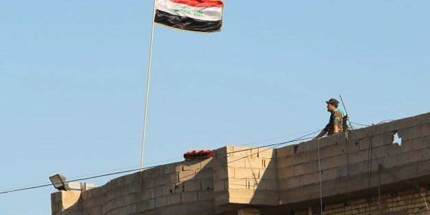 A member of Iraqi security forces stands on a roof on February 12, 2016, after security forces retook...