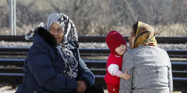 Afghan refugee women with a baby, rest on a blanket at the transit center for refugees near the northern...