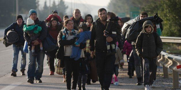Refugees and migrants make their way to reach the borderline to Macedonia, near the northern Greek village...