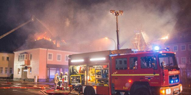 Fire fighters try to extinguish a fire at a former hotel that was under reconstruction to become a home...
