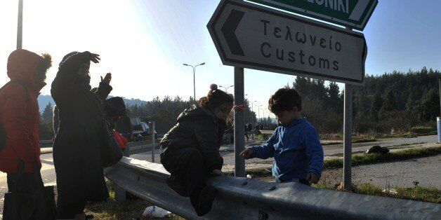 Children play as refugees and migrants walk to cross the Greek-Macedonian border near the village of...