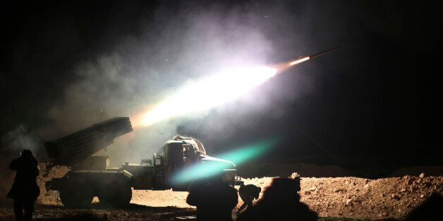 In this photo taken on Wednesday, Feb. 17, 2016, soldiers from the Syrian army fire a rocket at Islamic...