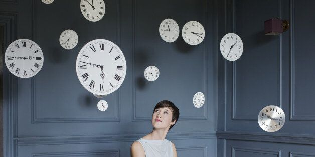 Woman in armchair with hanging clocks