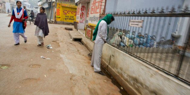 Varanasi, India. An Indian man urinates in the street while two girls walk behind