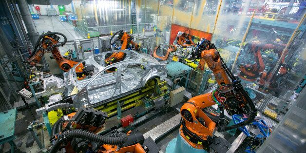Robotic arms, manufactured by Kuka AG, operate on the body shell of a Mercedes-Benz S-Class automobile...