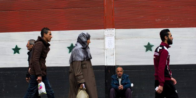 Syrians walk past a shop with a painting of the national flag in Damascus, Syria, Tuesday, Feb. 23, 2016....