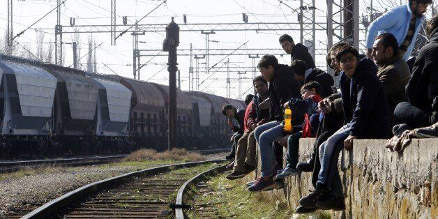 Refugees from Afghanistan sit beside railway tracks near a transit center for refugees at the Macedonian-Serbian...