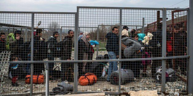 Migrants and refugees queue to board a train after crossing the Greek-Macedonian border near Gevgelija...