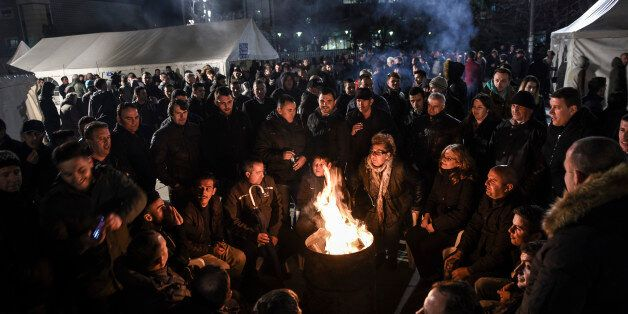 Opposition party supporters keep warm by a fire as they gather in front of Kosovo's government building...