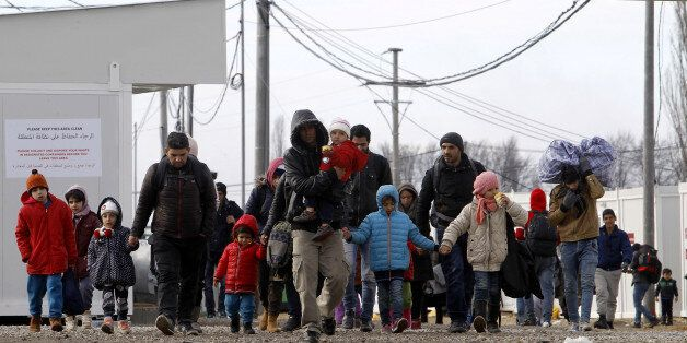 Refugees with children walk towards the border with Serbia from the transit center for refugees near...