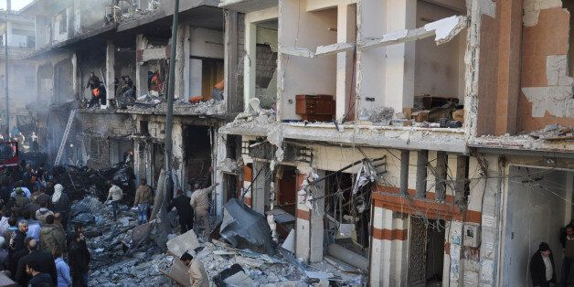 In this photo released by the Syrian official news agency SANA, Syrian citizens gather in front of damaged...