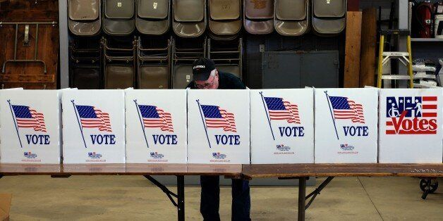 An elderly man votes for the first US presidential primary at a fire station in Loudon, New Hampshire,...