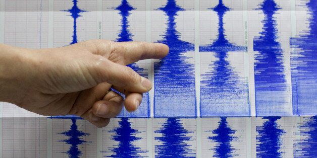 Taiwan's Central Weather Bureau official Lu Pei-ling points to seismograph readings of a 6.7 magnitude...