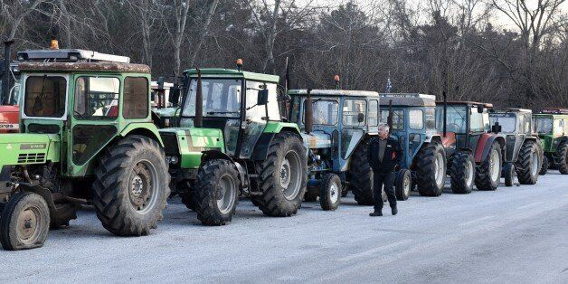 A protesting farmer walks next to parked tractors during a blockade in the northern Greek village of...