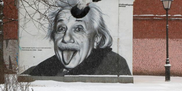 Pigeons fly past a portrait of Albert Einstein painted on a wall in St.Petersburg, Russia, Tuesday, Jan....