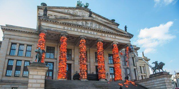 Assistants of Chinese artist Ai Weiwei decorate the columns of Berlin's Konzerthaus concert hall with...