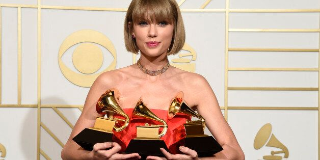 Taylor Swift poses in the press room with the awards for album of the year for 1989, pop vocal album for 1989 and best music video for