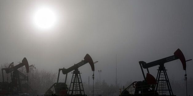 Pumping units, also known as 'nodding donkey's' or pumping jacks, stand silhouetted against the sun at...