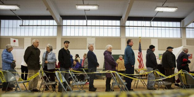 Voters wait in line to cast ballots at a polling station inside Broken Gound Elementary School in Concord,...