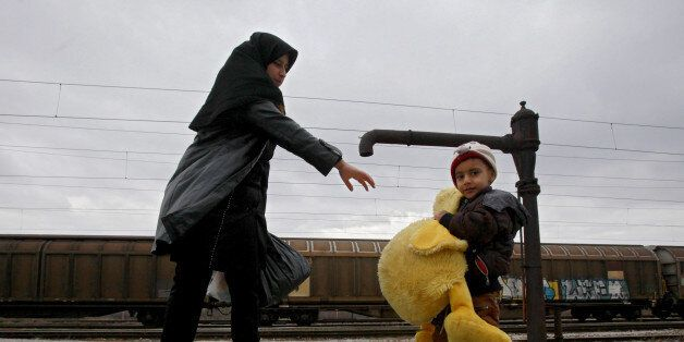 A refugee boy, carrying a giant stuffed duck, tries to catch up with his mother while both walk towards...