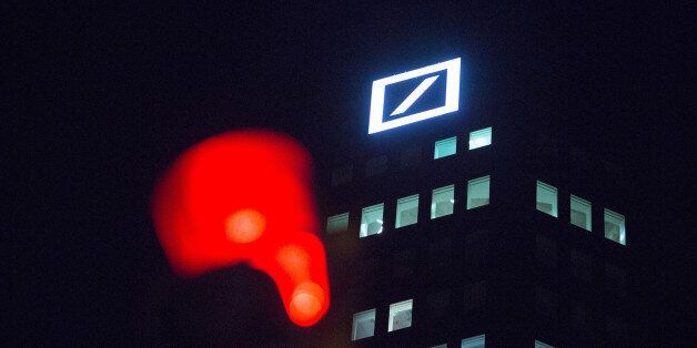 The Deutsche Bank AG, logo sits illuminated on the bank's headquarter offices at night in Frankfurt,...