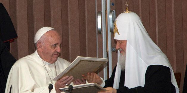 Pope Francis, left, and Russian Orthodox Patriarch Kirill exchange documents during their historic meeting...