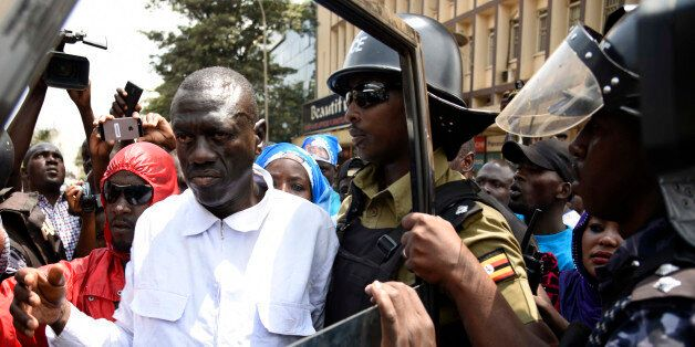 Uganda Anti-riot police officers arrest opposition leader, Kizza Besigye as he was walking on a busy...
