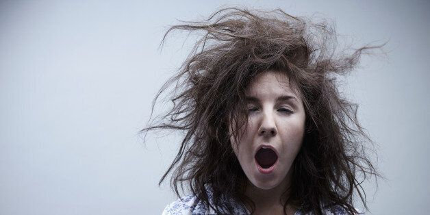 Young woman yawning, close