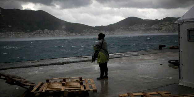 A migrant stands in front of a tent of the UNHCR at the registration center on the Greek island of Samos...
