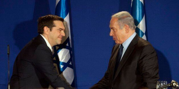 Greek Prime Minister Alexis Tsipras, right, and Israeli prime minister Benjamin Netanyahu shake hands...
