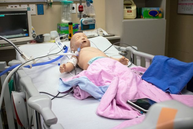 A baby mannequin used for training lies in a pediatric ICU bed at SickKids in Toronto. The baby can breathe...