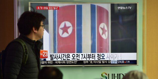 People watch a news report on North Korea's planned rocket launch as the television screen shows file...