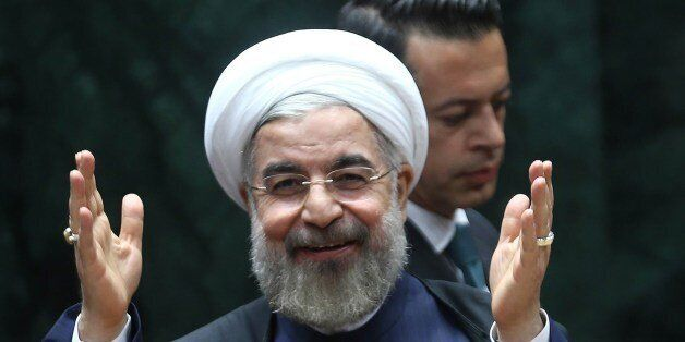 Iranian President Hassan Rouhani salutes before addressing a Turkish-Iranian bussines forum in Ankara...