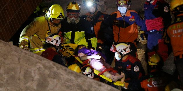 A female is rescued from a collapsed building complex after an early morning earthquake in Tainan, Taiwan,...
