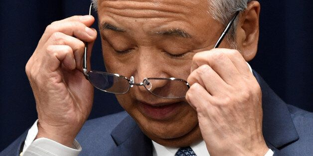 Japan's Economy Minister Akira Amari puts on his glasses during a press conference in Tokyo on January...