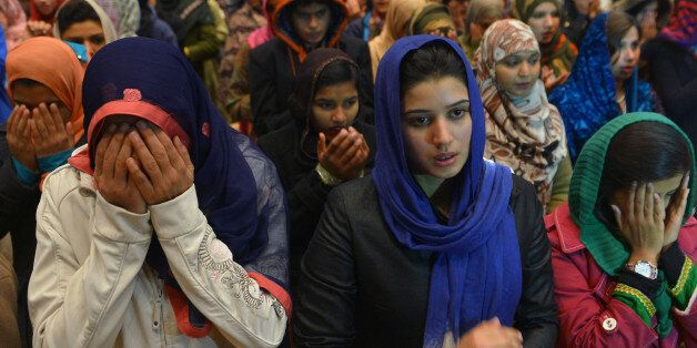 Pakistani women pray for Bacha Khan University victims at a sports complex in Islamabad on January 21,...