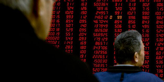 Chinese investors monitor stock prices on an electronic display in a brokerage house in Beijing, Friday,...