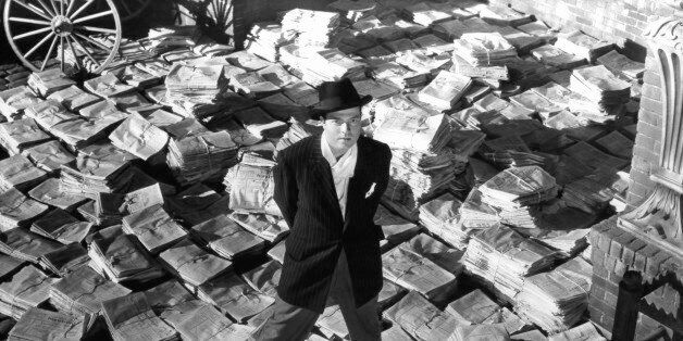 Orson Welles standing on stacks of newspapers in a scene from the film 'Citizen Kane', 1941. (Photo by...
