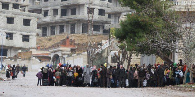 Residents of the besieged rebel-held Syrian town of Madaya wait for a convoy of aid from the Syrian Arab...