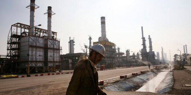 FILE - In this Dec. 22, 2014 file photo, an Iranian oil worker makes his way through Tehran's oil refinery...