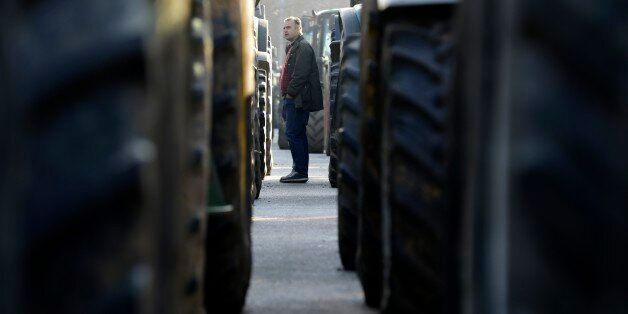 A man checks the tractors which were parked by protesting farmers in the northern Greek village of Promachonas...