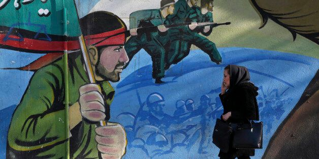 An Iranian woman walks past a mural depicting Iranian armed forces in the battlefield, at Palestine Sq....
