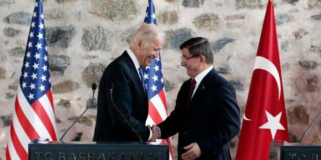 U.S. Vice President Joe Biden, left, shakes hands with Turkish Prime Minister Ahmet Davutoglu, right,...