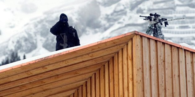 A Swiss police sniper stands on the roof of the Congress Center on January 25, 2011 on the eve of the...