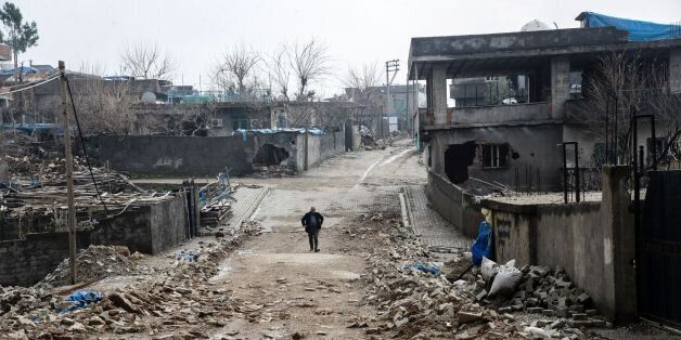 TOPSHOT - A man walks along a road damaged in the fighting between government troops and separatist Kurdistan...
