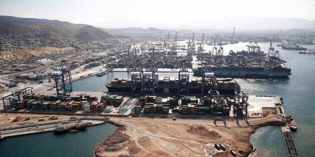 Container ships sit beneath gantry cranes at the COSCO Pacific Ltd. terminal at Piraeus port, operated...